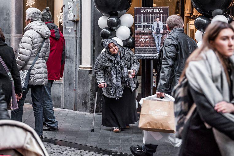 Een bedelaarster tussen het winkelende publiek in de Kleine Staat in Maastricht. Beeld HH / Roger Dohmen
