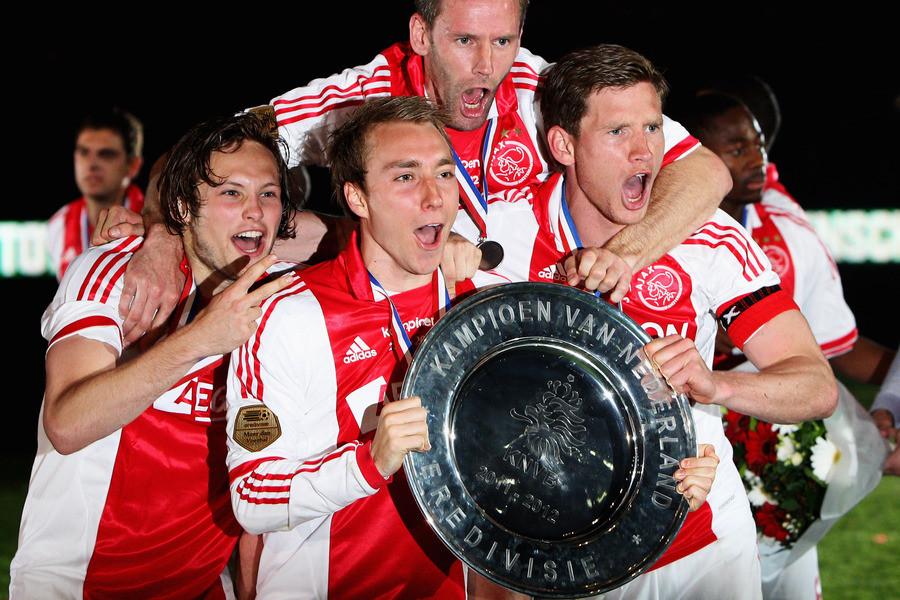 Daley Blind (links), Christian Eriksen (midden voor), Andre Ooijer (achter) en Jan Vertonghen (rechts) vieren het kampioenschap van Ajax.