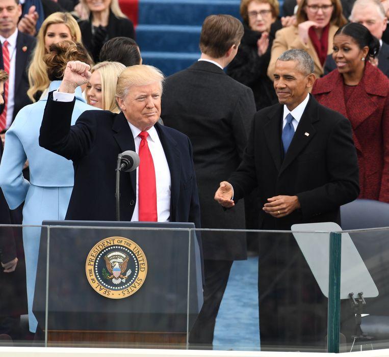 De Amerikaanse president Trump lacht na het afleggen van de presidentiële eed op 20 januari van dit jaar. Naast hem staat oud-president Obama.