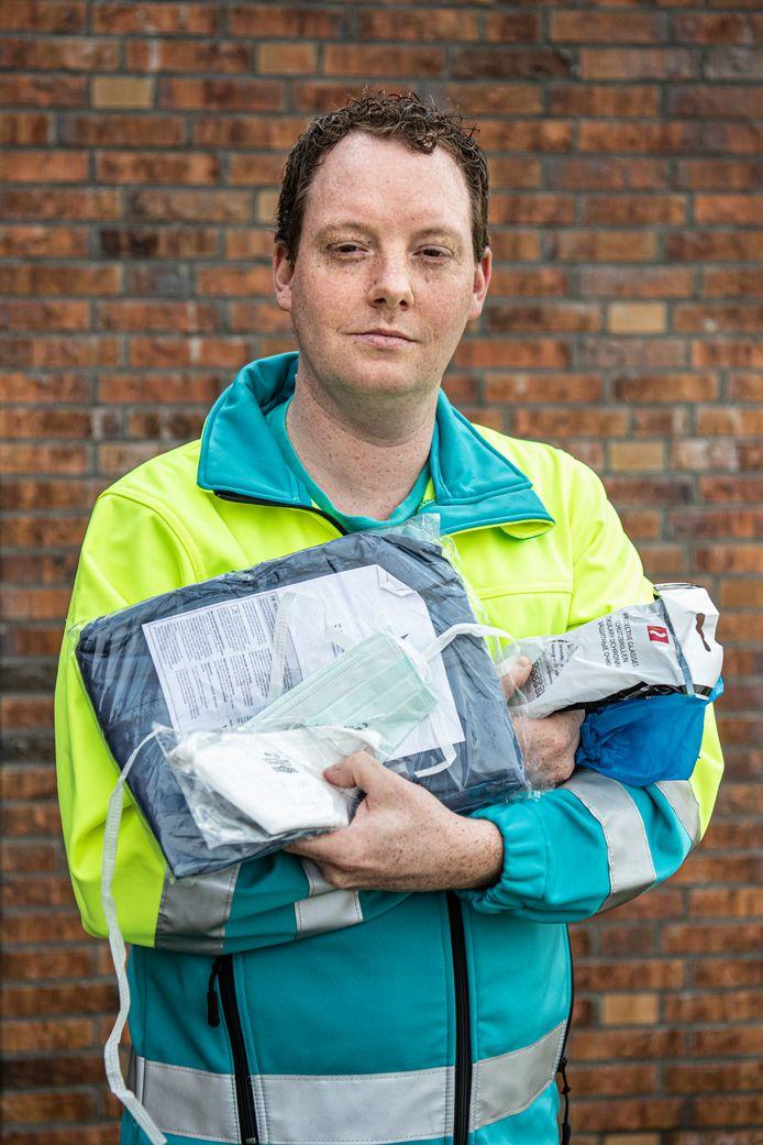 Ambulancebroeder Jan Hoefnagel heeft in zijn armen pakketjes met de beschermende kleding die hij bij de bezoeken aan coronapatiënten moet dragen. Zijn uitrusting: mondkapje, overall, hoesjes voor de schoenen, handschoenen en een spatbril.