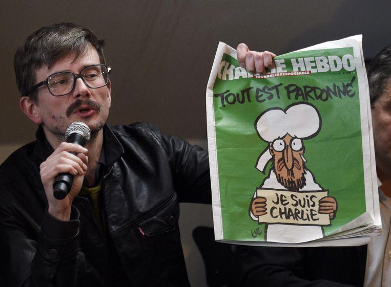 De Franse cartoonist Renald Luzier, Luz, met de cover van de nieuwe Charlie Hebdo. Beeld afp