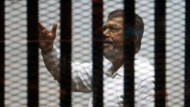 De afgezette Egyptische president Mohamed Morsi zwaait tijdens zijn proces naar zijn aanhangers. Beeld REUTERS