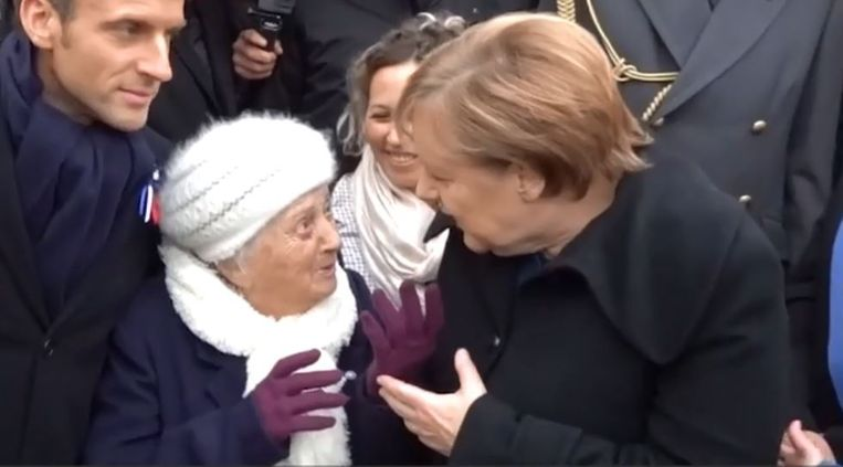 De Duitse bondskanselier Angela Merkel probeert het honderdjarige dametje uit te leggen dat ze de Duitse bondskanselier is en niet 'Madame Merkel'. Links kijkt de Franse president Macron geamuseerd toe.