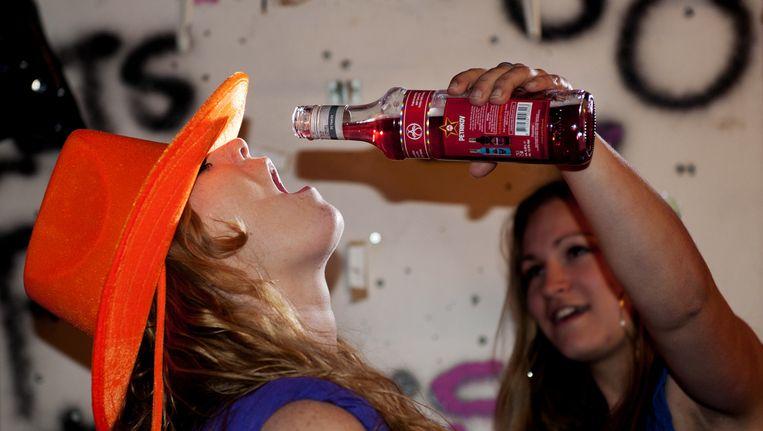 Een meisje voert een ander meisje drank. Beeld anp