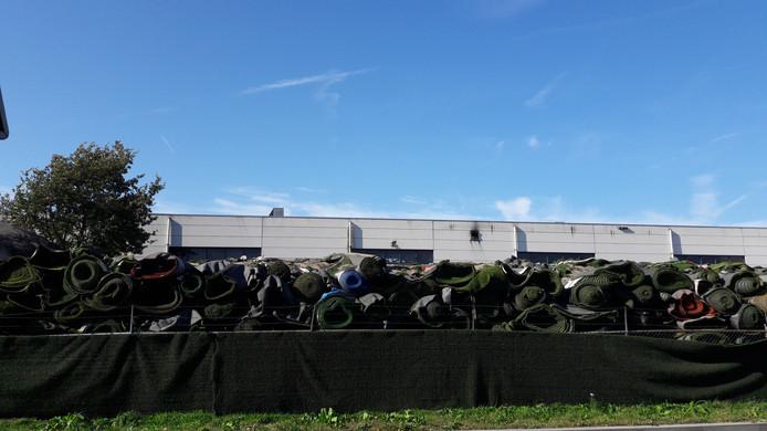 Hoog opgetaste rollen kunstgras en ontnemen in Dongen het zicht op de afgebrande loods van Tuf recycling. Die bevindt zich op het middenterrein. Achter een pand dat wel schade opliep, maar niet in as werd gelegd
