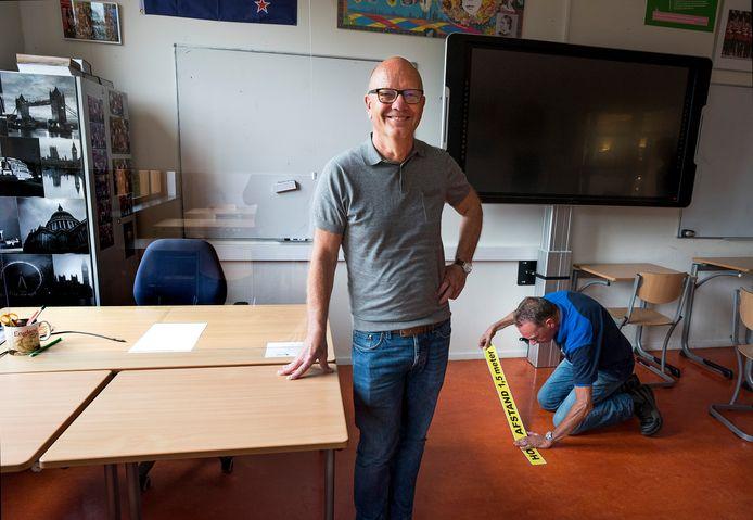 Han Koebrugge, locatiedirecteur van het Kalsbeek college in Woerden. De conciërge brengt een 1,5 metersticker aan.