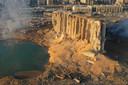 Een deel van de silo in de haven van Beiroet waar de explosieve stof lag opgeslagen staat nog overeind. Op de achtergrond de verwoeste stad.