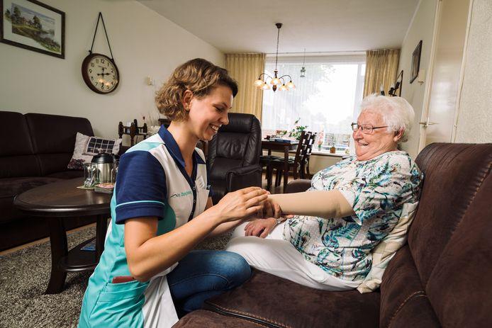 Een wijkverpleegkundige helpt een cliënte.
