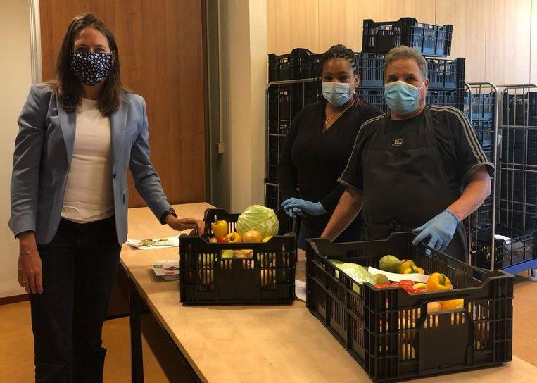 Wethouder Marjolein Moorman en twee vrijwilligers van Boeren voor Buren. Beeld Het Parool