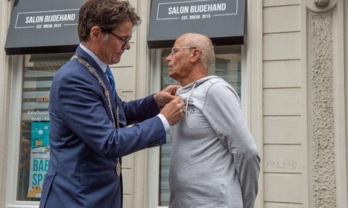 Burgemeester Paul Depla van Breda speldt de decoratie die hoort bij het lidmaatschap in de Orde van Oranje Nassu op bij Hans Holierhoek uit oosterhout.