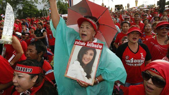 Een demonstrante houdt een foto van premier Yingluck Shinawatra vast.