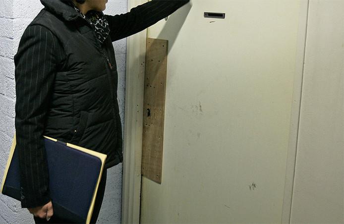 Foto ter illustratie. Een deurwaarder klopt op de deur.