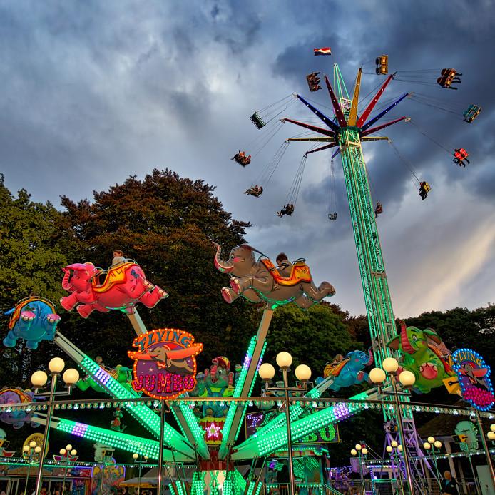 Archieffoto: kermis in het centrum van Oosterhout, hier in het Slotpark. Hoog vliegend op de rug van een olifant in de Flying Jumbo, of nog hoger in de stoeltjes van de Space Jam daar rechts achter, vangen de bezoekers de laatste zonnestralen.