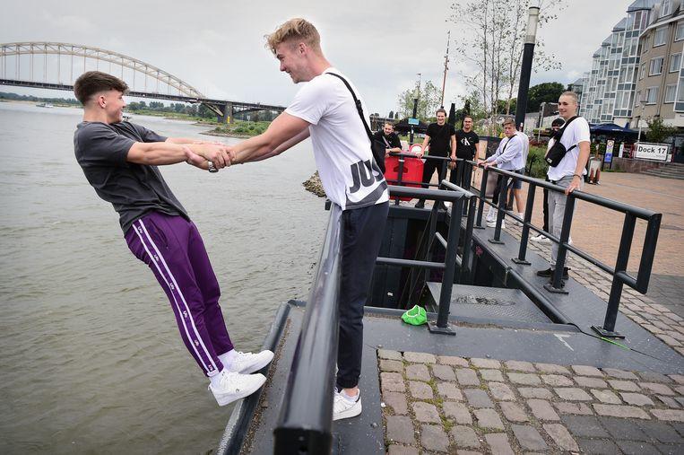 Jongens tarten de zwaartekracht op de Waalkade in Nijmegen. Beeld Marcel van den Bergh