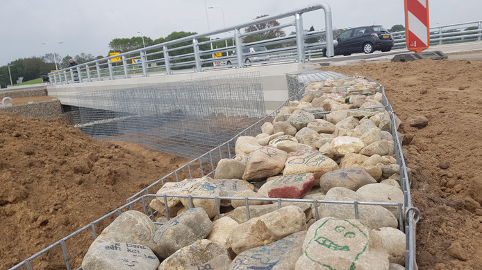 Versierde stenen in een van de schanskorven bij de N34.