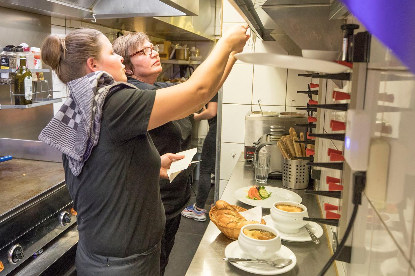 Renate Maas (links) en Kok Carola van Rookhuizen kijken tussen de bestellingen.