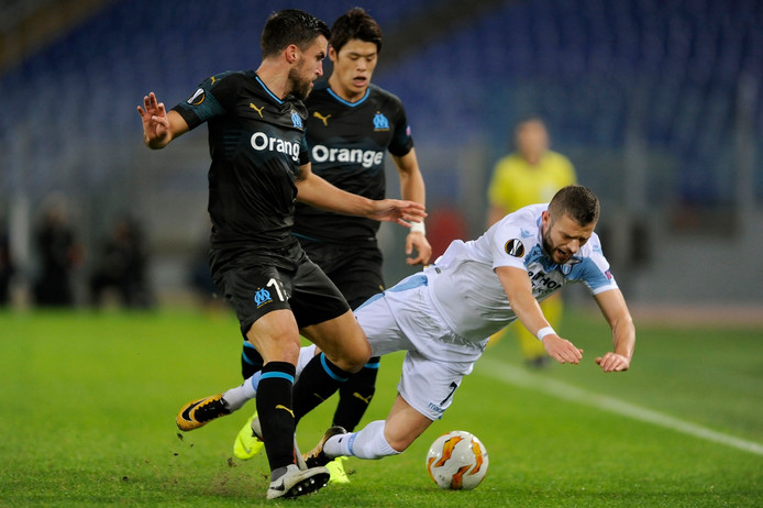 Kevin Strootman (links) laat Valon Berisha van Lazio struikelen.