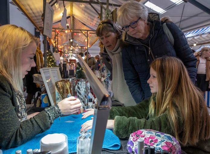 Nagelsyliste Samantha Bestebreurtje lakt de nagels van de 12-jarige Jessie van der Werf tijdens de Oosterlandse Winterfair.
