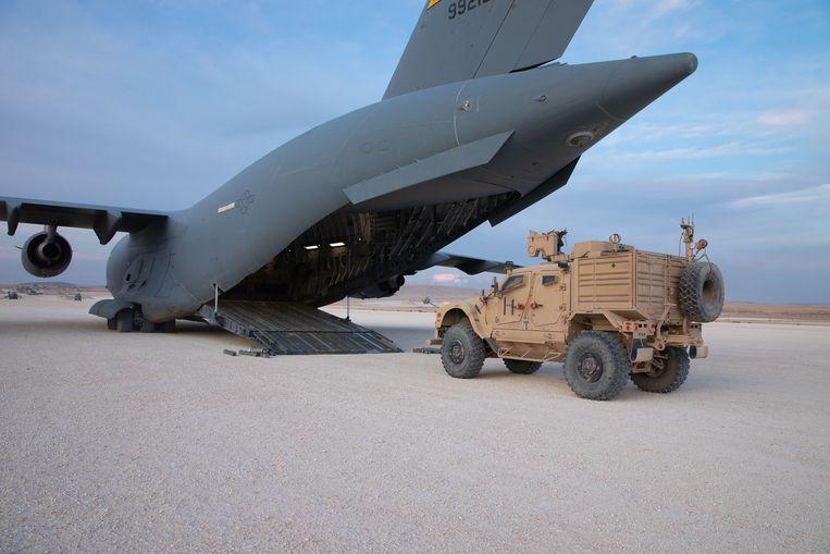 Legervoertuig wordt in een transportvliegtuig geladen op de Amerikaanse legerbasis bij Kobani, in Noord-Syrië.  Beeld EPA