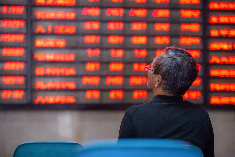 Een investeerder bekijkt de bewegingen op de beurs in Nanjing, China. Groen staat in China voor koersdalingen, rood voor winst.