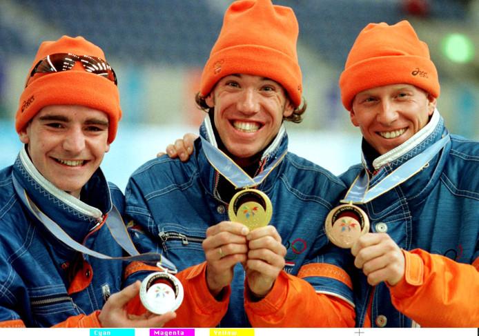 Olympische medailles in 1998 met lachende schaatsers Bob de Jong, Gianni Romme en Rintje Ritsma.