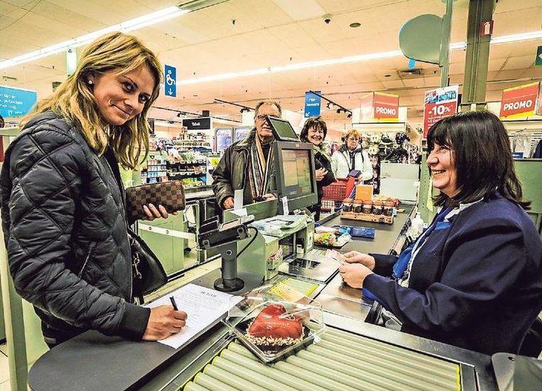 Een klant tekent de petitie aan de kassa van Christine De Paepe.