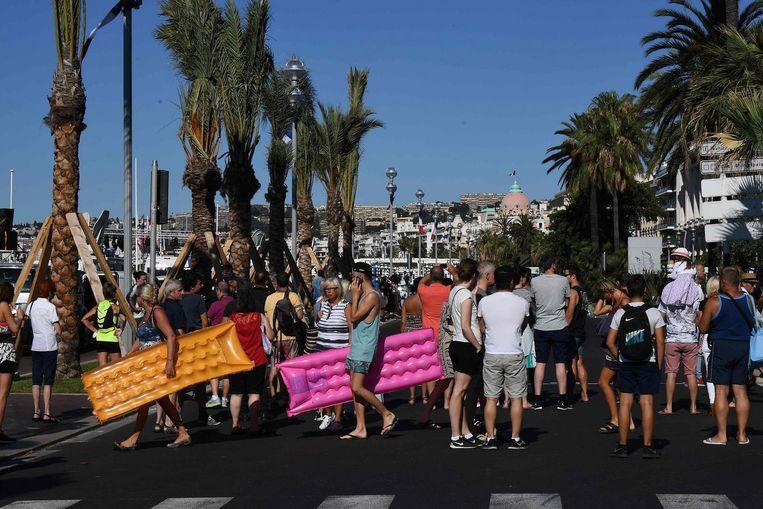 Omstanders praten na op de boulevard, anderen zijn op weg naar het strand. Beeld afp