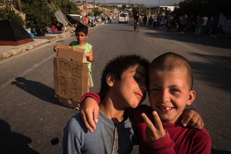 Twee kinderen poseren voor de camera tijdens een protest op de hoofdweg die van kamp Moria naar Mytilini leidt.  Beeld Nicola Zolin
