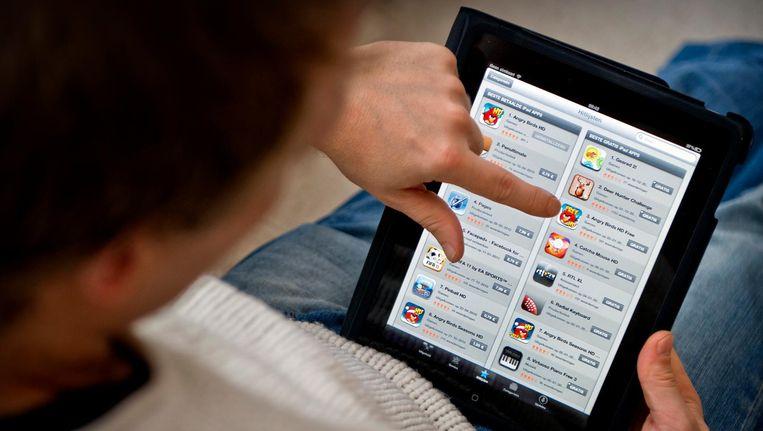 Jongen bekijkt App Store van Apple op een iPad. Beeld anp