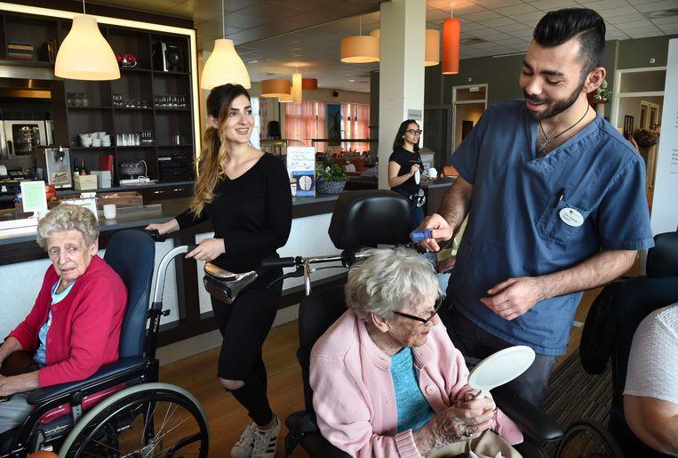 Vlnr de Griekse verpleegkundestudenten Tina, Vicky (op de achtergrond met bril) en Billy met mevrouw Martens. Beeld Marcel van den Bergh / de Volkskrant