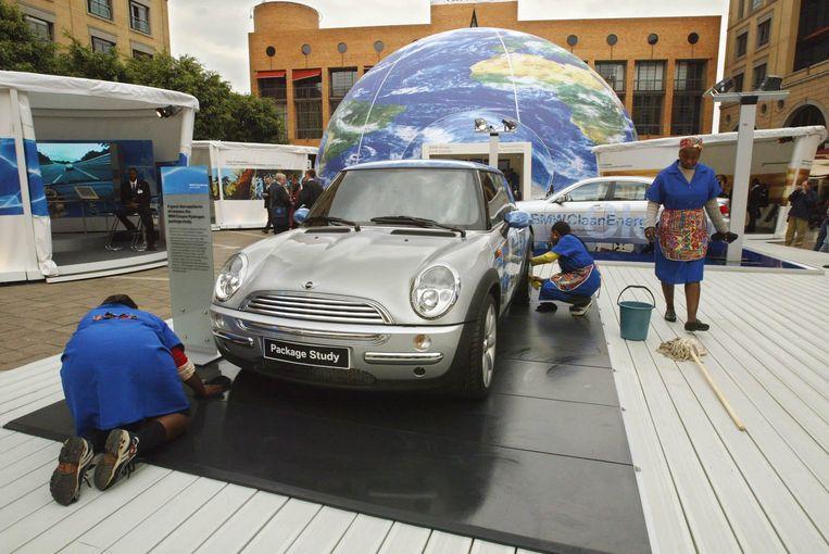 Schoonmakers poetsen een auto in het centrum van Johannesburg. Beeld AFPI