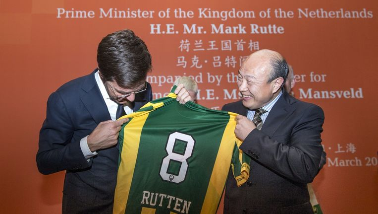 Premier Mark Rutte kijkt naar een shirt van ADO Den Haag met zijn fout gespelde naam erop dat hij kreeg van de nieuwe Chinese eigenaar van ADO, Hui Wang (R) tijdens de eerste dag van een 4-daags handelsmissie aan China. Beeld anp