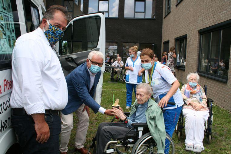 Burgemeester Stany De Rechter en schepen Kris Van Duyse delen ijsjes uit aan bewoners van WZC Vlashof.