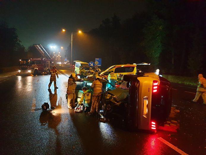 Brandweerlieden en ambulancemedewerkers helpen inzittenden van twee auto's na een aanrijding op de Amersfoortseweg ter hoogte van de Zandbergenlaan.