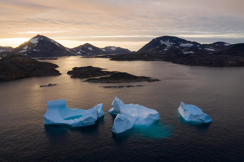 IJsbergen drijven weg bij zonsopgang bij Kulusuk, een nederzetting op Groenland. Beeld AP