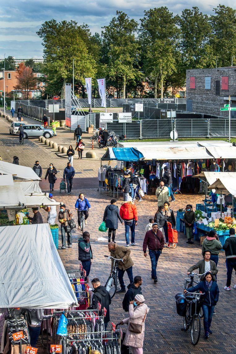 De Bijlmermarkt in Amsterdam, met op de achtergrond de nieuwe coronateststraat van de GGD. Beeld Raymond Rutting / de Volkskrant