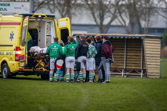 Bezorgde spelers van Blokzijl kijken hoe Roelof van der Linde de ambulance in gaat.