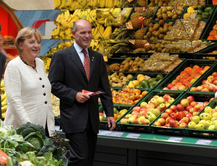 Karl-Erivan Haub (rechts) ontvangt de Duitse bondskanselier Angela Merkel in een van zijn supermarkten.