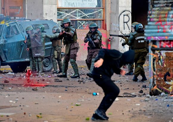 De Chileense oproerpolitie richt hun geweren op een demonstrant in Santiago.