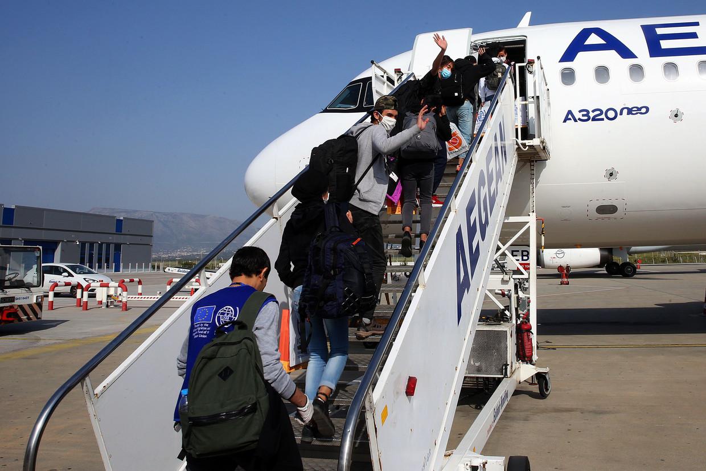 Minderjarige asielzoekers gaan het vliegtuig in onderweg naar Luxemburg.  Beeld AFP