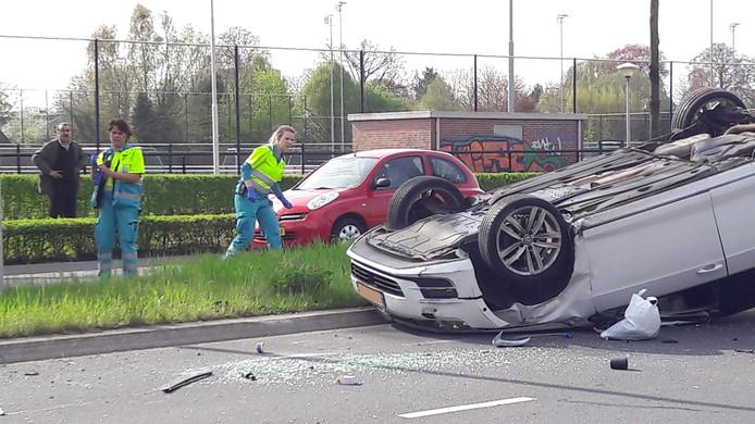 Ambulancepersoneel kijkt of er nog iemand in de gecrashte auto zit.