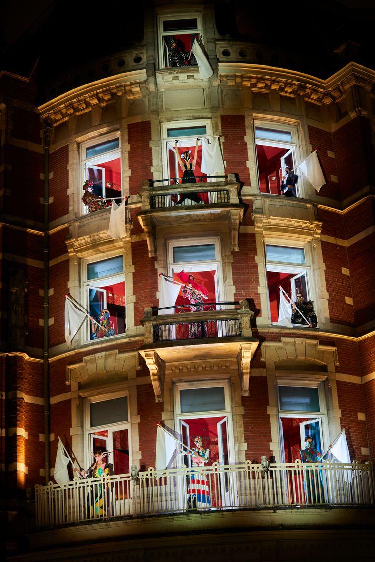 Vlagzwaaiende modellen gekleed in jurken en mondmaskers van Ronald van der Kemp tijdens de performance 'Army of Love' op de balkons van Hotel de l'Europe in Amsterdam, 28 april 2020. Beeld Marijke Aerden