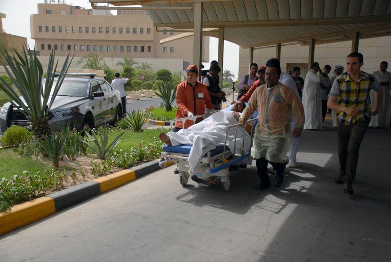 Een slachtoffer van de aanslag in Koeweit wordt naar het ziekenhuis gebracht. Beeld reuters