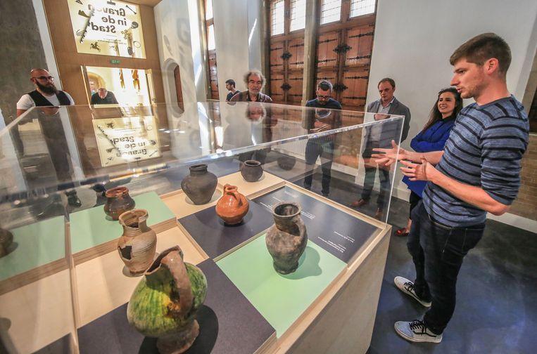 Archeoloog Jan Decorte geeft wat uitleg bij enkele kruiken die bij de opgravingen werden gevonden.