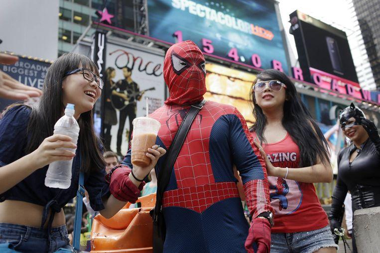 Een man verkleed als Spider-Man poseert met toeristen op Times Square. Beeld ap