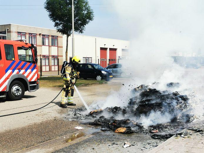 De brandweer blust op de Microweg in Nijmegen de brandende en smeulende lading van de vuilniswagen.