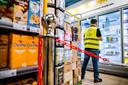 Een vakkenvuller doet zijn werk en houdt klanten op veilige afstand.