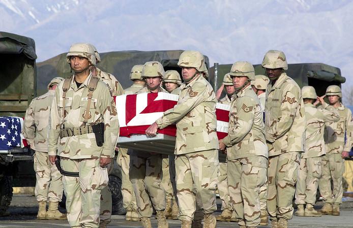 Amerikaanse soldaten dragen een gesneuvelde helikopterpiloot tijdens een ceremonie op luchtmachtbasis Bagram.