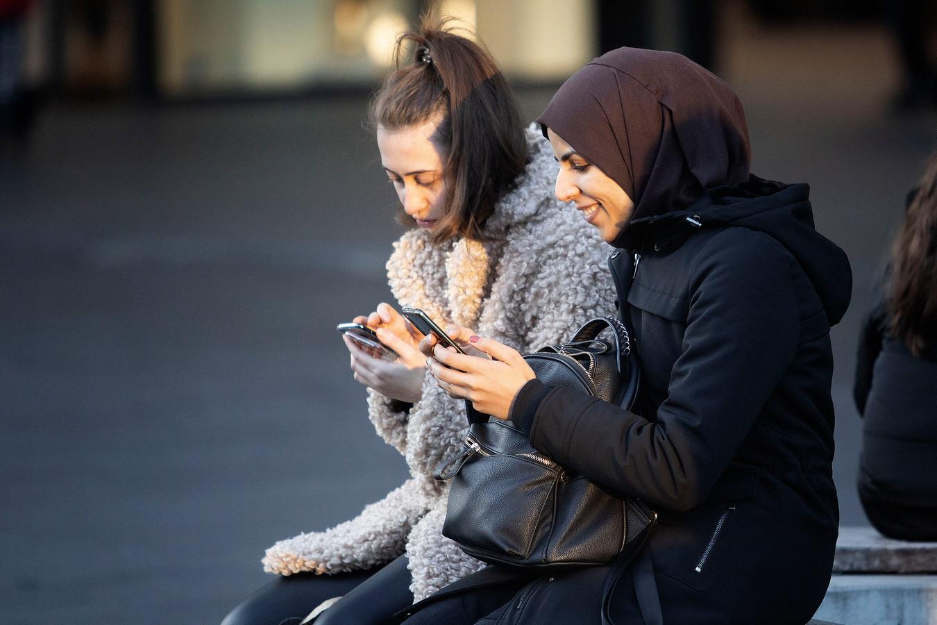 Jongeren die op hun smartphone kijken zijn een vast onderdeel van het straatbeeld geworden.