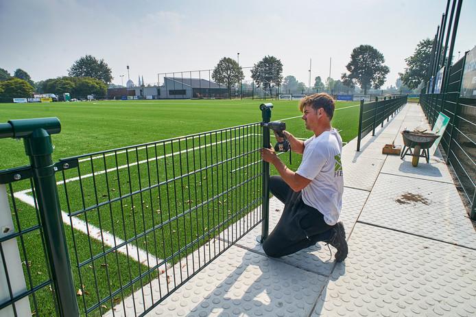 Er wordt nog hard gewerkt aan de afrastering rond het nieuwe kunstgrasveld van FC de Rakt. De verlichting laat nog even op zich wachten.